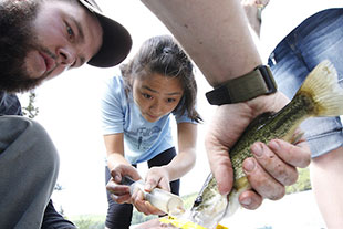 Photo of students holding a fish. Link to Closely Held Business Stock.